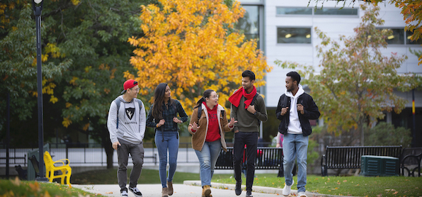 5 students walking in the quad with fall colours in the background