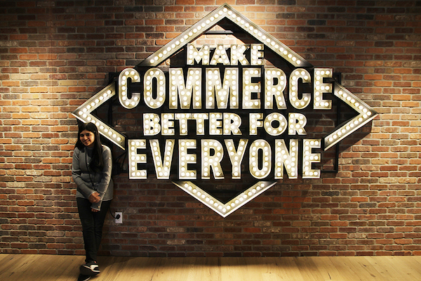 Ketki in front of Shopify sign Make Commerce Better for Everyone