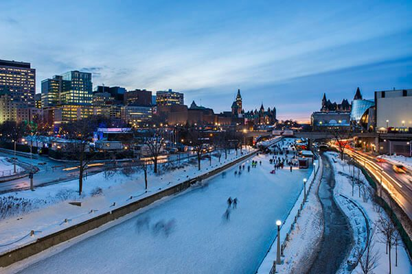 People skate on the Rideau Canal at night.