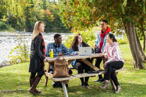 Students study near the Rideau River on campus.
