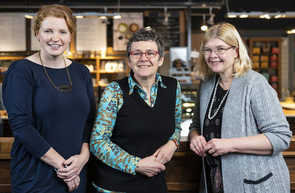 Kate Burnett, Tracey Clark and Dana Brown stand together in a Bridgehead coffees shop location.