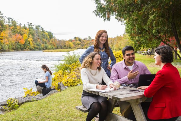 Students sit by the Rideau River